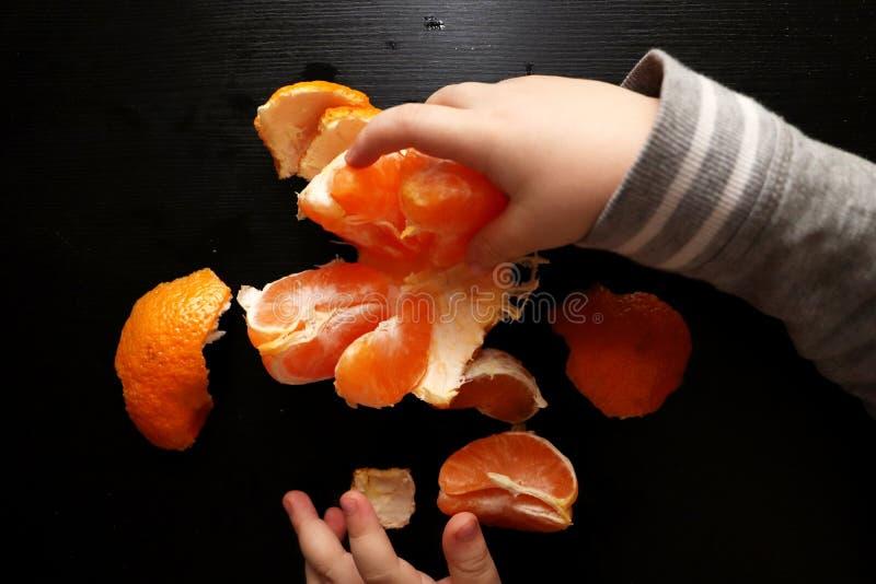 Τα χέρια των παιδιών βουρτσίζουν το μανταρίνι σε ένα μαύρο υπόβαθρο Το παιδί φθάνει για μια φέτα του μανταρινιού στοκ φωτογραφία