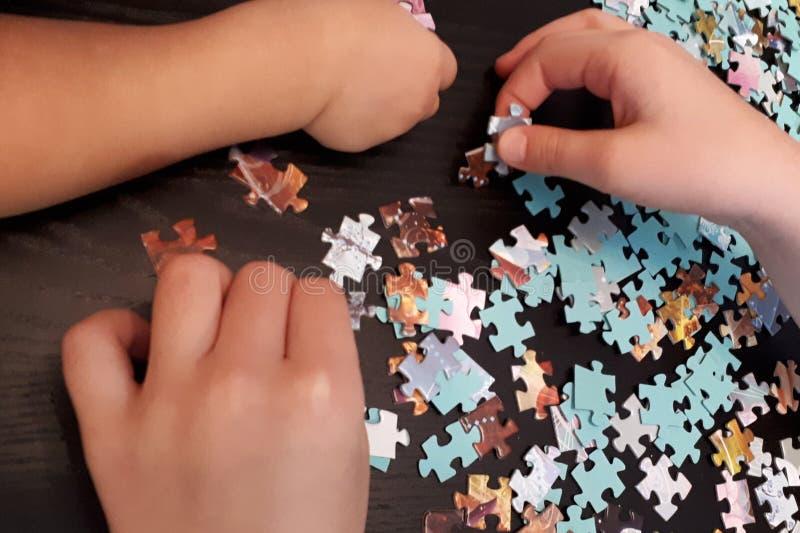 Τα χέρια των παιδιών συλλέγουν τους γρίφους στοκ εικόνα με δικαίωμα ελεύθερης χρήσης