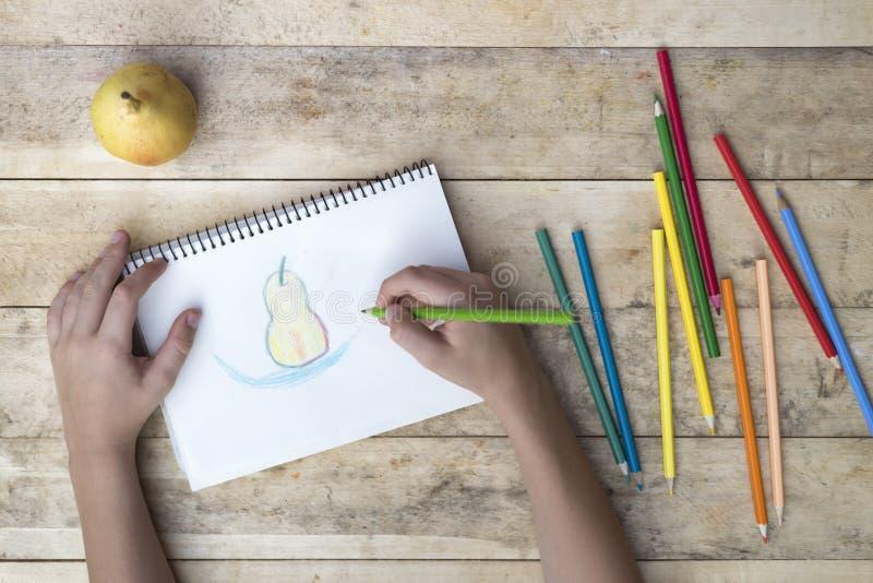 Τα χέρια των παιδιών σύρουν ένα αχλάδι με τα χρωματισμένα μολύβια Τοπ όψη στοκ εικόνες με δικαίωμα ελεύθερης χρήσης