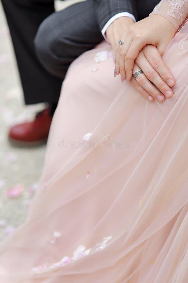 Τα χέρια των newlyweds newlyweds κρατούν το γάμο χεριών στοκ εικόνα