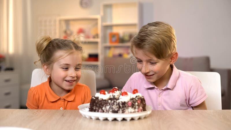 Τα χαμογελώντας παιδιά που εξετάζουν τη σοκολάτα συσσωματώνουν στον πίνακα, ευτυχία παιδικής ηλικίας, δώρο στοκ εικόνες
