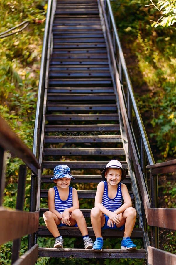 Τα χαμογελώντας παιδιά το καλοκαίρι Παναμάς και τα σορτς κάθονται στα βήματα το καλοκαίρι Κάθετη φωτογραφία στοκ εικόνα
