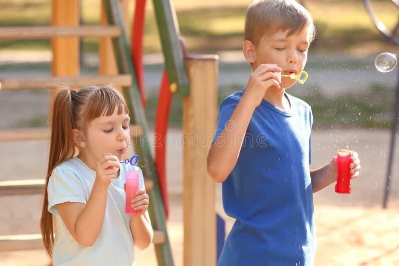 Τα χαριτωμένα μικρά παιδιά που φυσούν το σαπούνι βράζουν υπαίθρια στοκ εικόνα με δικαίωμα ελεύθερης χρήσης