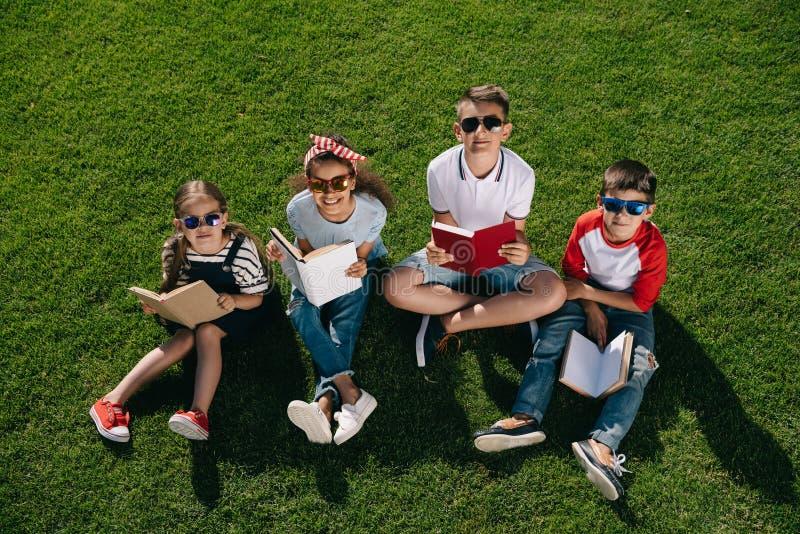 Τα χαριτωμένα multiethnic παιδιά στην ανάγνωση γυαλιών ηλίου κρατούν καθμένος στη χλόη και το χαμόγελο στοκ εικόνες με δικαίωμα ελεύθερης χρήσης