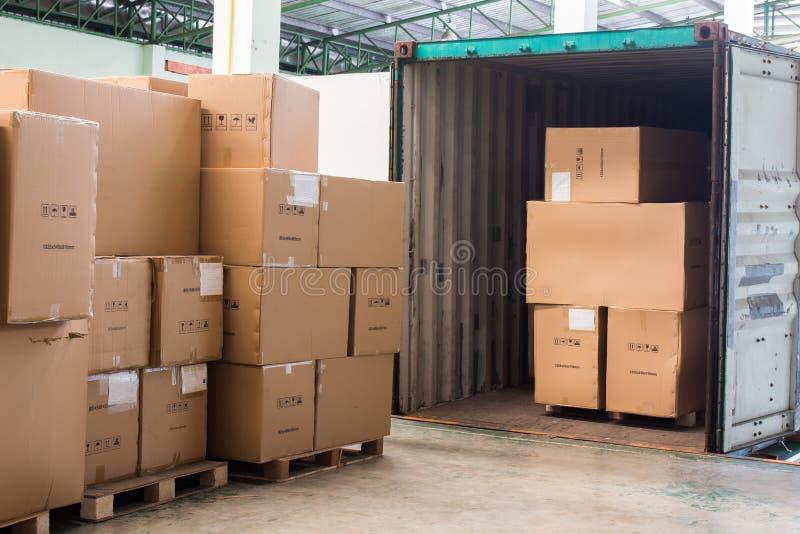 Τα χαρτοκιβώτια με τη φόρτωση από το εμπορευματοκιβώτιο στοκ εικόνες