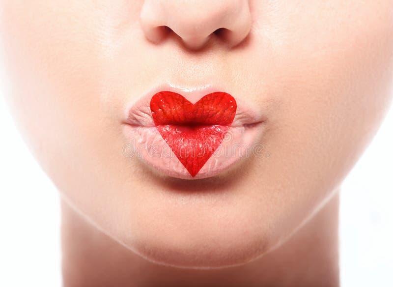 Τα χείλια φιλήματος με το καλό κόκκινο αποτελούν στην καρδιά στοκ εικόνες