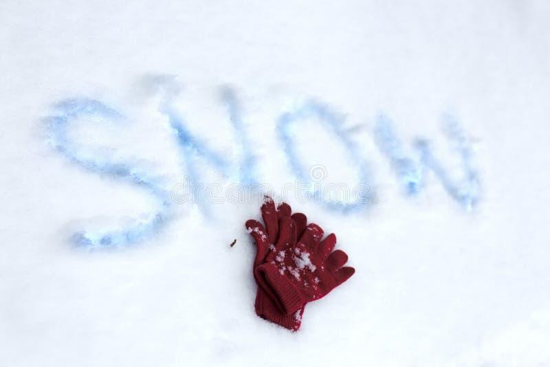 Τα χειμερινά γάντια βάζουν στο χιόνι με το χιόνι επιγραφής στοκ εικόνα