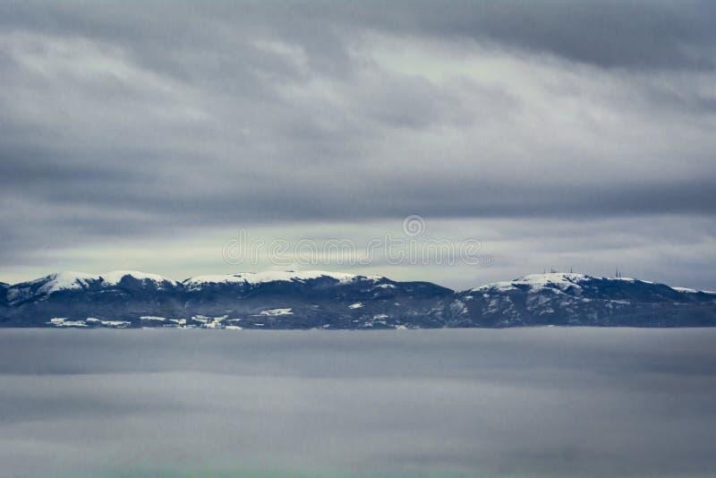 Τα χιονοσκεπή βουνά στον παγωμένο σαφή χειμερινό ουρανό βλαστάνουν από μια θάλασσα των σύννεφων στοκ φωτογραφία με δικαίωμα ελεύθερης χρήσης