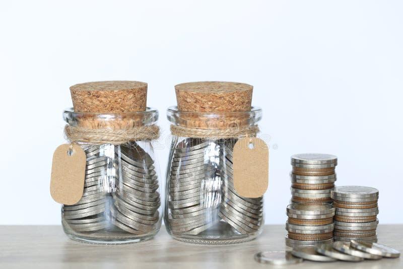 Τα χρήματα αποταμίευσης για προετοιμάζουν στο μέλλον την έννοια, το σωρό των χρημάτων νομισμάτων και το μπουκάλι γυαλιού στο υπόβ στοκ εικόνες