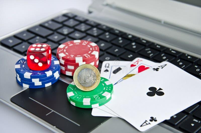 Τα χρήματα, κάρτες παιχνιδιού, χωρίζουν σε τετράγωνα και τα τσιπ χαρτοπαικτικών λεσχών στο πληκτρολόγιο υπολογιστών στοκ εικόνες