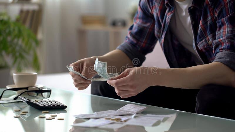 Τα χρήματα υπολογισμού ατόμων έφυγαν στον επόμενο μισθό, φτωχό αρσενικό που κερδίζει τα χρήματά του, χρηματοδότηση στοκ φωτογραφία με δικαίωμα ελεύθερης χρήσης