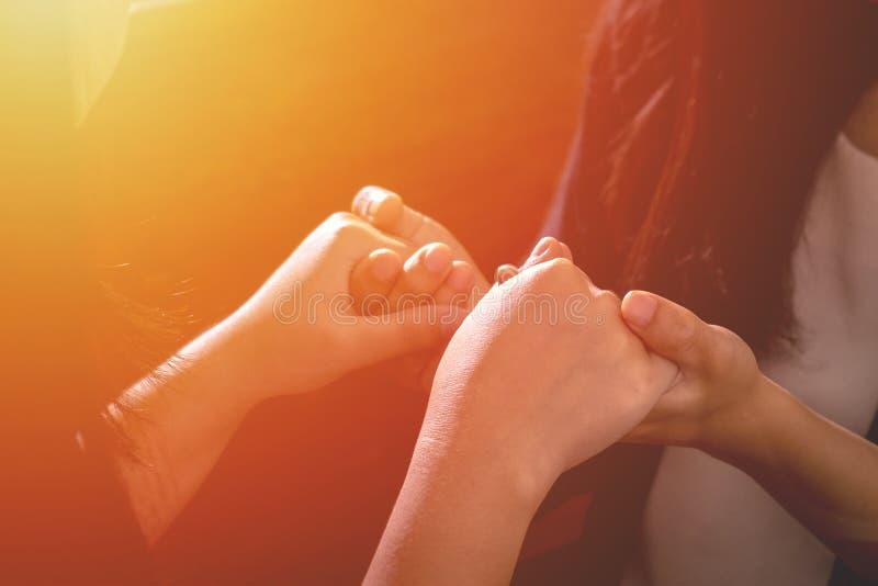 Τα χριστιανικά θηλυκά χέρια εκμετάλλευσης φίλων ζεύγους μαζί και προσεύχονται το τ στοκ εικόνες