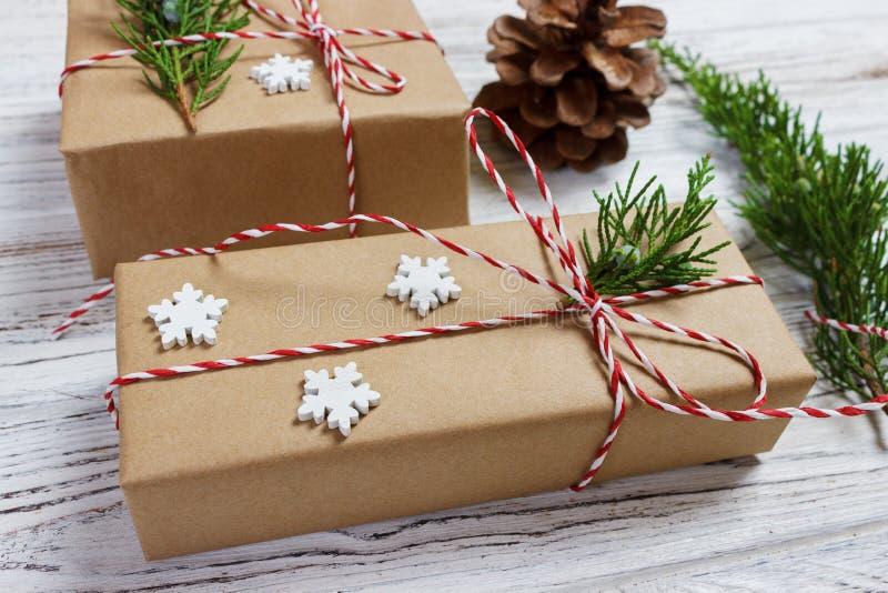 Τα Χριστούγεννα ή το νέο έτος παρουσιάζουν τυλιγμένος στο φυσικό χρωματισμένο έγγραφο και διακοσμημένος με τους παραδοσιακούς κλα στοκ εικόνες με δικαίωμα ελεύθερης χρήσης
