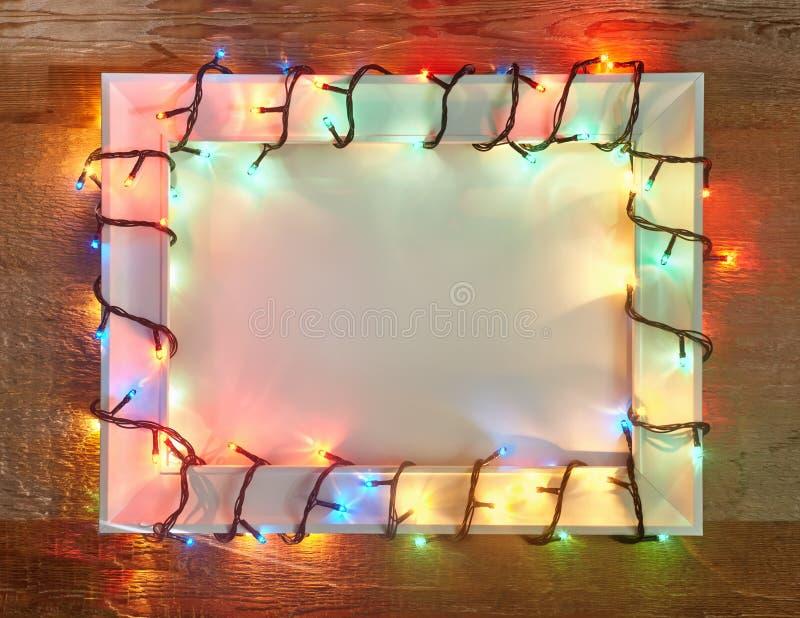 Τα Χριστούγεννα ανάβουν το πλαίσιο στο ξύλινο υπόβαθρο με το διάστημα αντιγράφων στοκ εικόνες