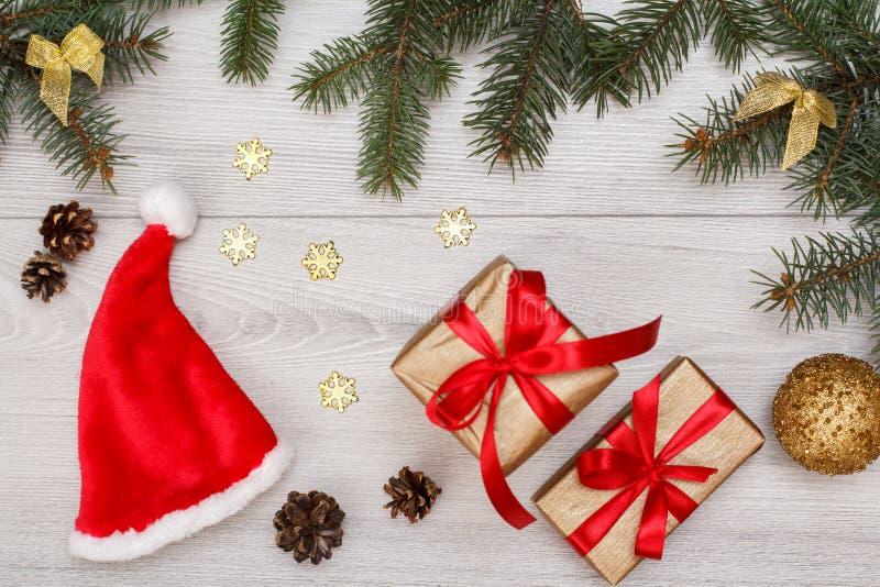 τα Χριστούγεννα διακοσμούν τις φρέσκες βασικές ιδέες διακοσμήσεων Το καπέλο του Santa, κιβώτια δώρων, δέντρο έλατου διακλαδίζεται στοκ φωτογραφίες