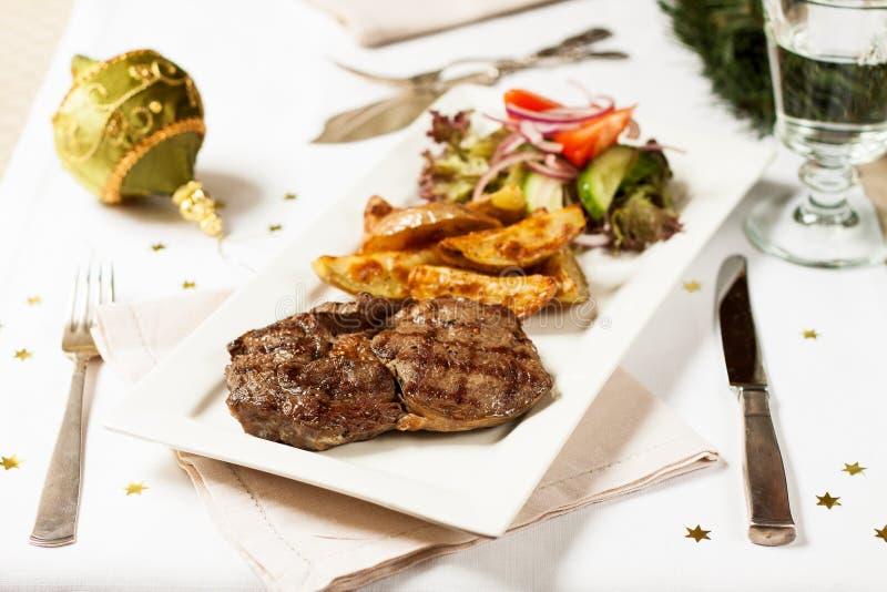 τα Χριστούγεννα διακοσμούν τις φρέσκες βασικές ιδέες γευμάτων Μπριζόλα βόειου κρέατος με τις ψημένες πατάτες στοκ εικόνα με δικαίωμα ελεύθερης χρήσης