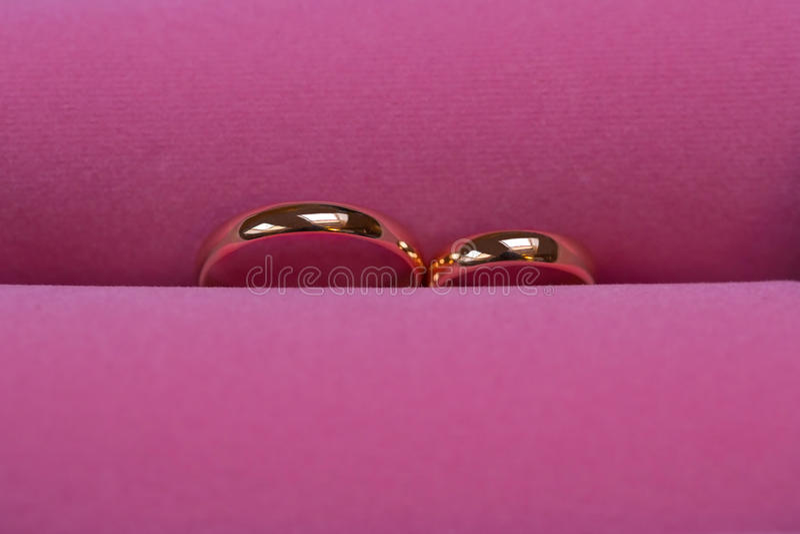 Download Τα χρυσά γαμήλια δαχτυλίδια στο ρόδινο υπόβαθρο, κλείνουν επάνω Στοκ Εικόνες - εικόνα από αγάπη, παρόν: 62716084