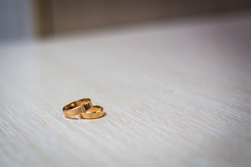 Τα χρυσά δαχτυλίδια δέσμευσης το ένα στο άλλο βρίσκονται σε μια ελαφριά επιφάνεια ο γάμος χτυπά κοντά επάνω, τοποθετημένος ο ένας στοκ φωτογραφίες με δικαίωμα ελεύθερης χρήσης