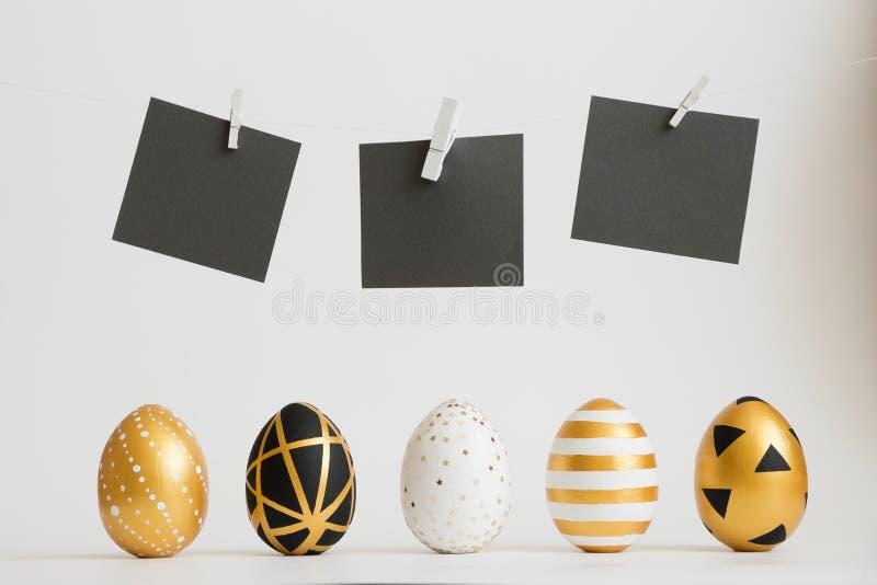 Τα χρυσά διακοσμημένα αυγά Πάσχας στέκονται σε μια σειρά με τις μαύρες αυτοκόλλητες ετικέττες κειμένων επάνω από τους στο άσπρο υ ελεύθερη απεικόνιση δικαιώματος