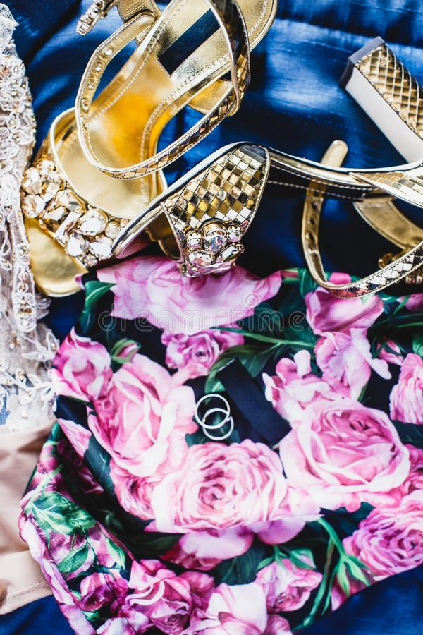 Τα χρυσά υψηλά τακούνια και ένα ζευγάρι των δαχτυλιδιών βρίσκονται σε ένα μπλε φόρεμα με το floral σχέδιο στοκ εικόνα με δικαίωμα ελεύθερης χρήσης