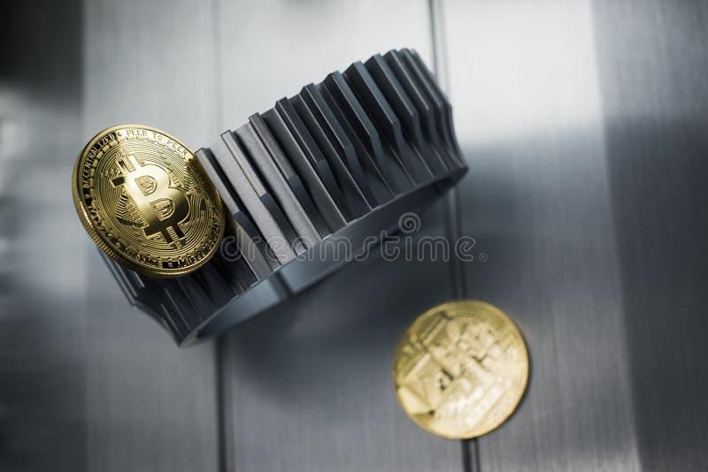Τα χρυσά bitcoins βρίσκονται gearwheel μετάλλων στοκ φωτογραφία