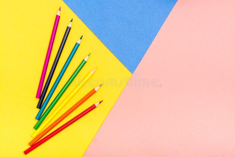 Τα χρωματισμένα μολύβια βρίσκονται όπως έναν ανεμιστήρα σε ένα υπόβαθρο tricolor στοκ εικόνα με δικαίωμα ελεύθερης χρήσης
