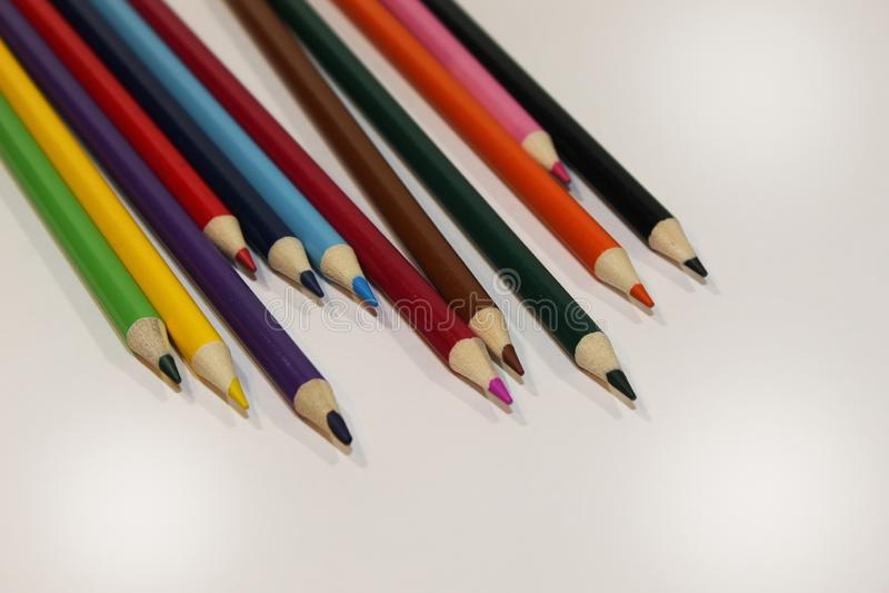 Τα χρωματισμένα μολύβια διασκόρπισαν την αριστερή γωνία στοκ εικόνες