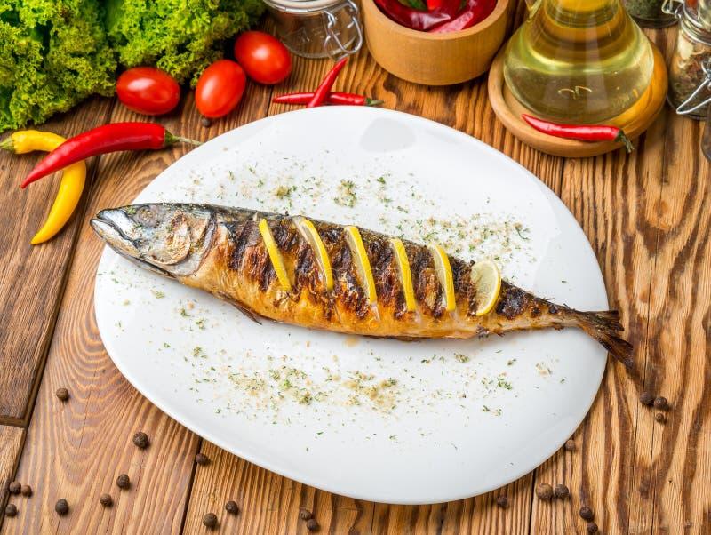 Τα ψάρια μαγείρεψαν στην πυρκαγιά ένα άσπρο πιάτο με τα φύλλα μαρουλιού και το λεμόνι μαϊντανού στοκ φωτογραφία