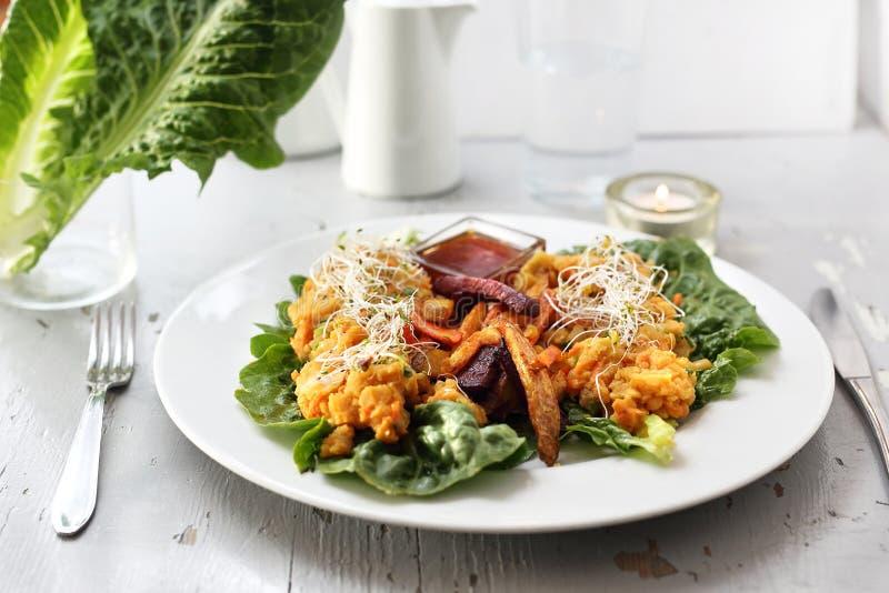 Τα ψημένα λαχανικά, γλυκιά πατάτα, πατάτα, σέλινο, καρότο, τεύτλο εξυπηρέτησαν με φυτικό stew στο μαρούλι παγόβουνων στοκ φωτογραφία