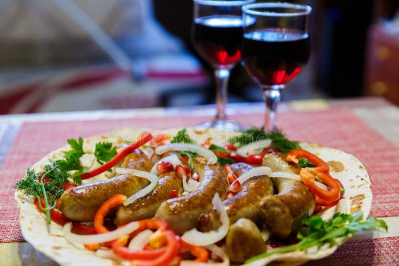Τα ψημένα στη σχάρα λουκάνικα χοιρινού κρέατος στο ψωμί pita με τα λαχανικά εξυπηρετούνται με το κόκκινο κρασί Τρόφιμα Oktoberfes στοκ φωτογραφίες με δικαίωμα ελεύθερης χρήσης