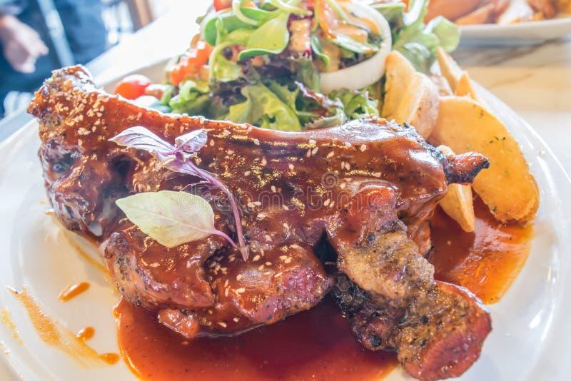 Τα ψημένα στη σχάρα πλευρά χοιρινού κρέατος στο άσπρο πιάτο διακόσμησαν με τη σαλάτα και τηγάνισαν την πατάτα στοκ φωτογραφία με δικαίωμα ελεύθερης χρήσης