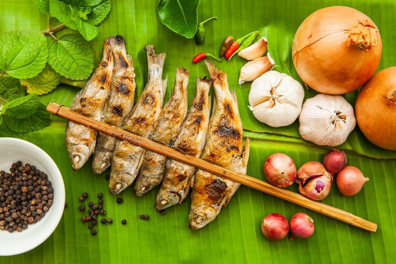 Τα ψημένα στη σχάρα ψάρια και το κρεμμύδι, σκόρδο, τσίλι, πιπέρι, kaffir ασβεστώνουν τα φύλλα στα φύλλα μπανανών στοκ εικόνες