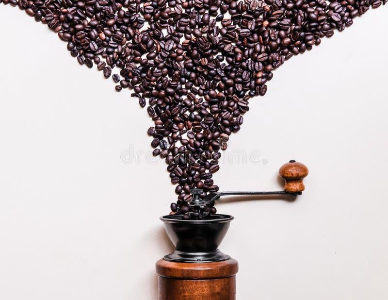 Τα ψημένα φασόλια καφέ που μειώνονται στον αναδρομικό ξύλινο μύλο στο άσπρο υπόβαθρο αντιγράφουν το διάστημα στοκ φωτογραφία