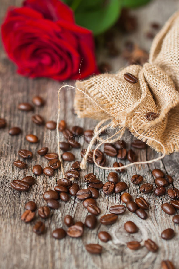 Τα ψημένα φασόλια καφέ, φρέσκος κόκκινος αυξήθηκαν, χονδροειδής burlap σάκος στον παλαιό ξύλινο πίνακα ζωή αγροτική ακόμα τοποθετ στοκ φωτογραφία