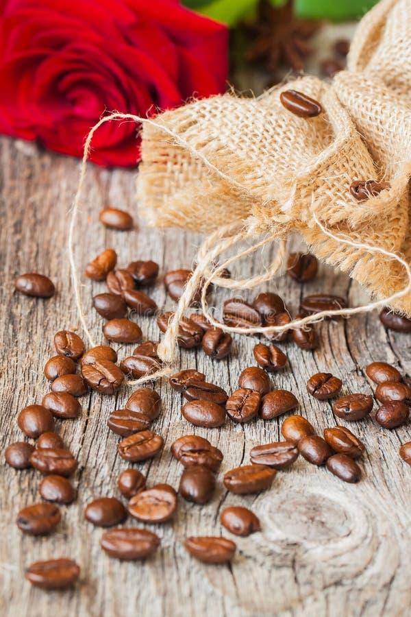 Τα ψημένα φασόλια καφέ, φρέσκος κόκκινος αυξήθηκαν, χονδροειδής burlap σάκος στον παλαιό ξύλινο πίνακα ζωή ακόμα εκλεκτής ποιότη& στοκ φωτογραφία με δικαίωμα ελεύθερης χρήσης