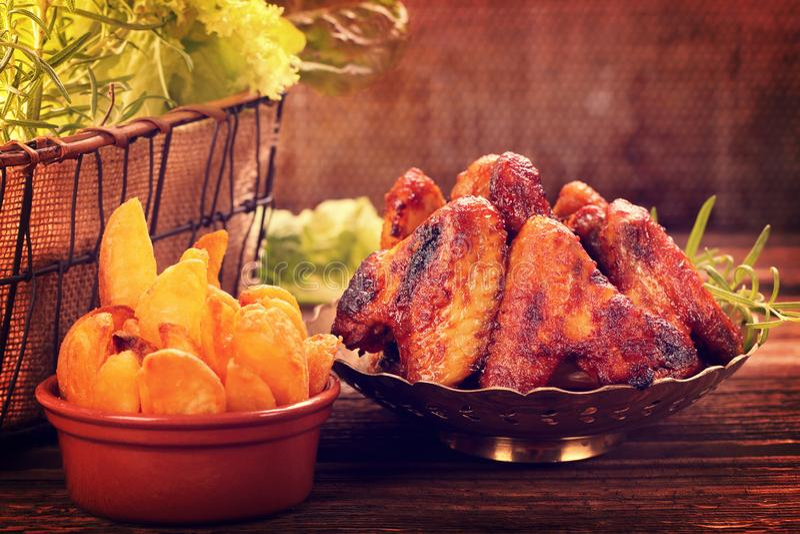 Τα ψημένα φτερά κοτόπουλου με την ψημένη πατάτα στον πίνακα, κλείνουν επάνω την εκλεκτής ποιότητας άποψη στοκ εικόνες με δικαίωμα ελεύθερης χρήσης