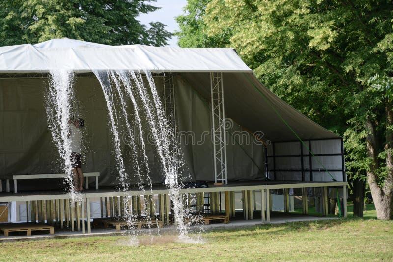 Τα όμβρια ύδατα ωθούνται από έναν θόλο επάνω από το στάδιο προτού να αρχίσει το φεστιβάλ στοκ φωτογραφία με δικαίωμα ελεύθερης χρήσης