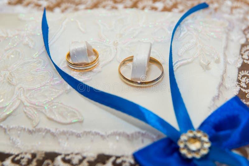 Τα όμορφα γαμήλια δαχτυλίδια βρίσκονται σε ένα μαξιλάρι με την άσπρη δαντέλλα και τις μπλε κορδέλλες υπό μορφή τόξου στοκ εικόνα με δικαίωμα ελεύθερης χρήσης