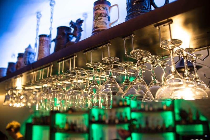 Τα όμορφα γυαλιά κοκτέιλ στο φραγμό κρεμούν πέρα από τον πίνακα nightclub Τα οινοπνευματώδη ποτά, πολλά γυαλιά κρασιού έχουν τις  στοκ φωτογραφία με δικαίωμα ελεύθερης χρήσης