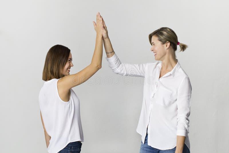 Τα όμορφα ελκυστικά αστεία χαλαρωμένα ξένοιαστα κορίτσια χαιρετούν στο άσπρα πουκάμισο και τα τζιν στοκ φωτογραφία με δικαίωμα ελεύθερης χρήσης