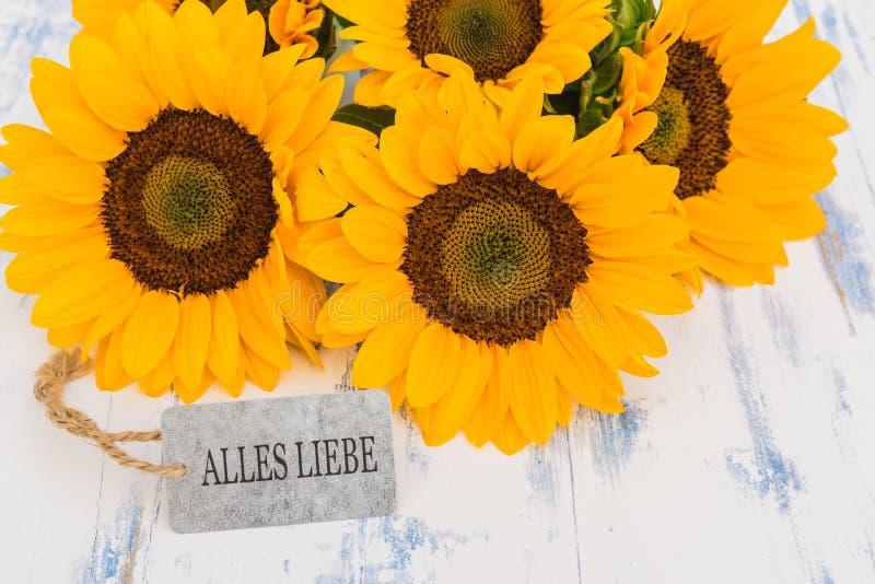 Τα όμορφα κίτρινα λουλούδια με τη ευχετήρια κάρτα με το γερμανικό κείμενο, Alles Liebe, σημαίνουν τις καλύτερες ευχές στοκ φωτογραφία με δικαίωμα ελεύθερης χρήσης