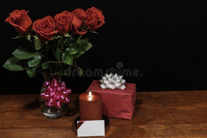 Τα όμορφα κόκκινα τριαντάφυλλα στο βάζο με το ρόδινο τόξο τύλιξαν το παρόν και κόκκινο κερί με την ετικέττα ονόματος στον ξύλινο  στοκ φωτογραφία με δικαίωμα ελεύθερης χρήσης