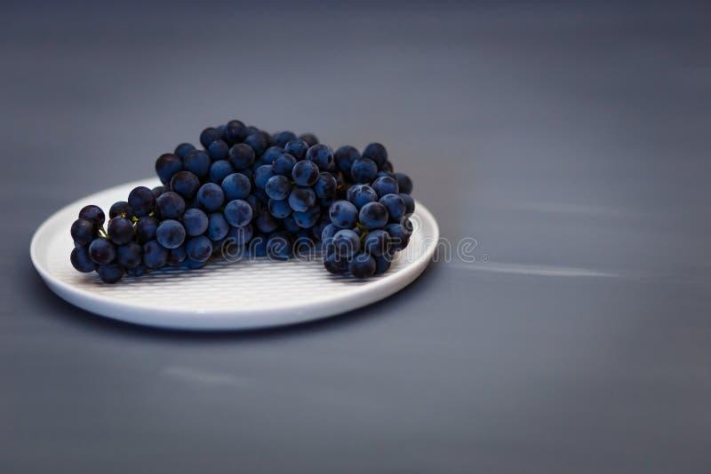 Τα όμορφα μαύρα μπλε σταφύλια Isabella βρίσκονται σε ένα άσπρο πιάτο στοκ φωτογραφία