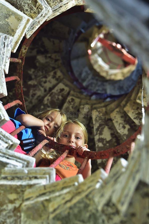 Τα όμορφα μικρά κορίτσια στην πέτρα κινούνται σπειροειδώς σκάλα ένας παλαιός φάρος στοκ εικόνα με δικαίωμα ελεύθερης χρήσης
