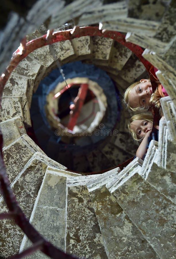 Τα όμορφα μικρά κορίτσια στην πέτρα κινούνται σπειροειδώς σκάλα ένας παλαιός φάρος στοκ εικόνες με δικαίωμα ελεύθερης χρήσης