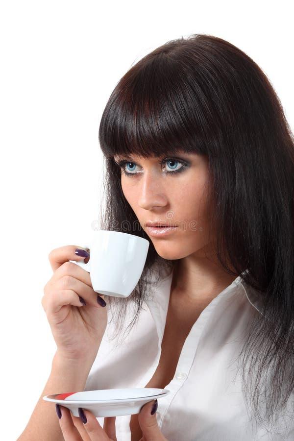 Τα όμορφα μπλε μάτια πίνουν τον καφέ στοκ εικόνα