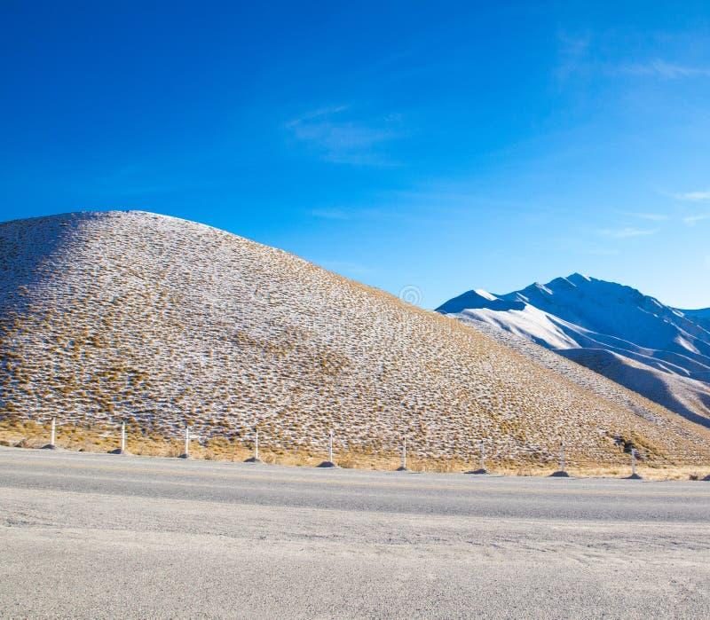 Τα όμορφα ξηρά χιονώδη βουνά με το υπόβαθρο μπλε ουρανού στο νότιο νησί, Νέα Ζηλανδία στοκ εικόνα