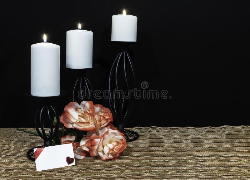 Τα όμορφα πορτοκαλιά και άσπρα τριαντάφυλλα, άσπρο κερί εσκαρφάλωσαν στους μαύρους κατόχους κεριών στο χαλί θέσεων πλέγματος και  στοκ εικόνες με δικαίωμα ελεύθερης χρήσης