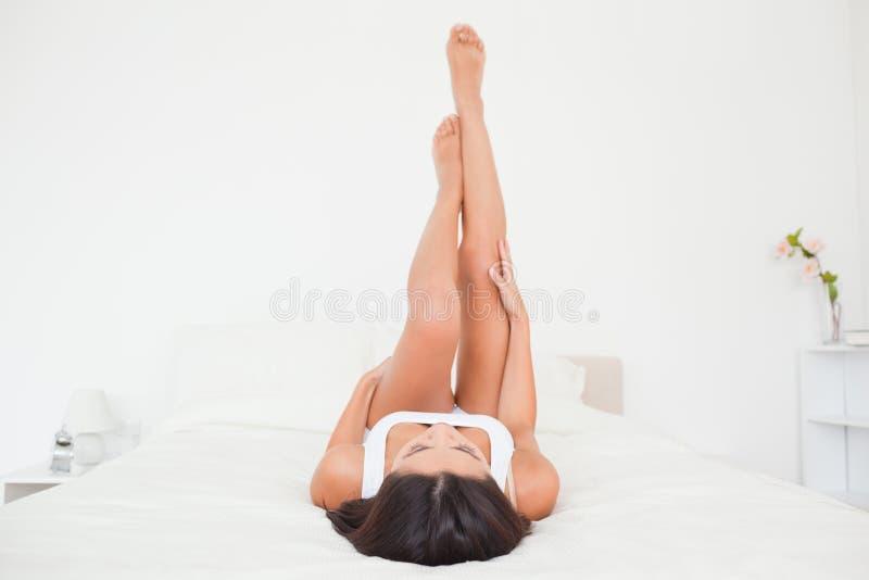 Τα όμορφα πόδια γυναικών αύξησαν επάνω υψηλά να βρεθούν στο σπορείο στοκ φωτογραφία