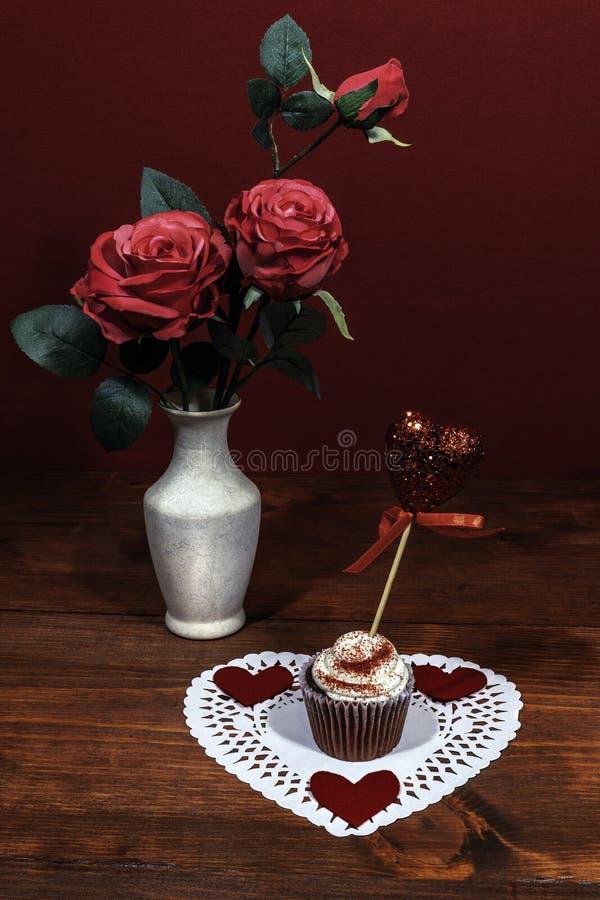 Τα όμορφα ρόδινα τριαντάφυλλα σε ένα βάζο, καρδιά το άσπρο dollie με ένα διακοσμημένο κέικ φλυτζανιών σε το με μια καρδιά σε μια  στοκ εικόνες